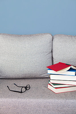 Stack of books on a sofa - p4540854 by Lubitz + Dorner