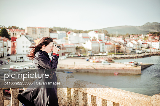 Brunette woman in dark coat taking photos from the top of a viewpoint - p1166m2255986 by Cavan Images