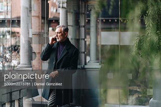Fashionable mature male talking on mobile phone while standing by glass wall at hotel - p300m2273781 by Daniel González