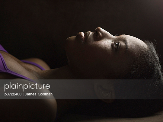 Portrait of African-American woman laying on back - p3722400 by James Godman