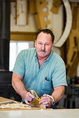 Portrait of confident carpenter carving wood at workshop - p1166m1544038 by Cavan Images