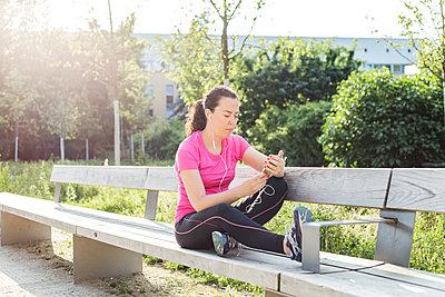 Junge Sportlerin auf Bank im Park. - p1396m1463546 von Hartmann + Beese