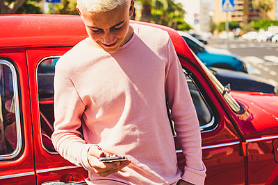 Smiling teenage boy standing in front of vintage car looking at smartphone - p300m2203009 by Simona Pilolla