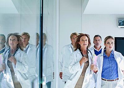 Female and male doctors running down a corridor, Cape Town, South Africa - p300m2281407 von LOUIS CHRISTIAN