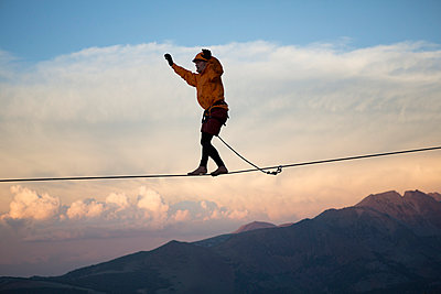 Male highliner walks a 125 foot highline over mountains in a gap on top of Mammoth Crest  - p343m1003003f by Jared Alden