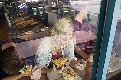 Caucasian woman eating pizza in cafe - p555m1305737 by Sam Diephuis
