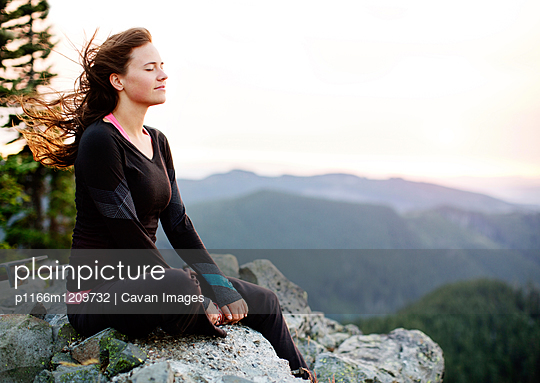 Woman meditating while sitting on rock formation against clear sky - p1166m1209732 by Cavan Images