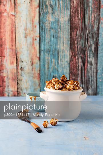 Caramel popcorn in bowl - p300m1581417 von Mandy Reschke