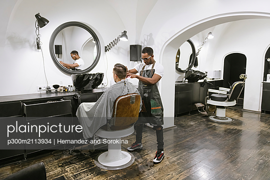 Barber cutting hair of a customer in barber shop - p300m2113934 by Hernandez and Sorokina