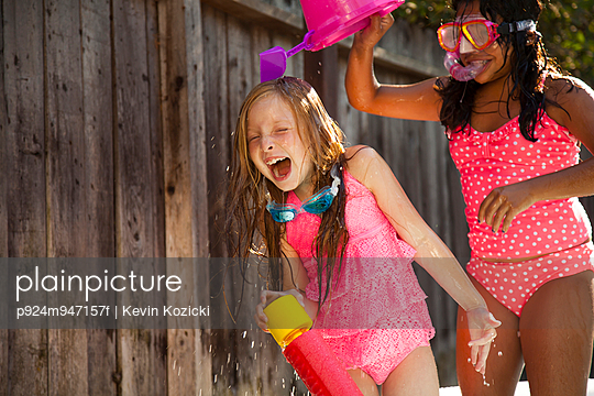 Two girls chasing each other with water in garden - p924m947157f by Kevin Kozicki