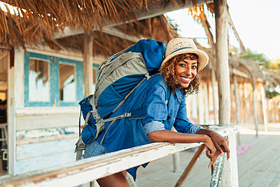 Portrait happy young female backpacker on beach hut patio - p1023m2135764 by Paul Bradbury