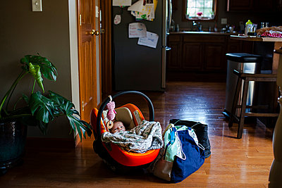 High angle view of new born resting in baby seat by luggage at home - p1166m1183010 by Cavan Images