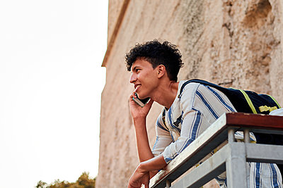 Young man with afro hair is using his smartphone outdoors - p1166m2201816 by Cavan Images