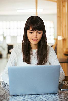 Portrait of young woman using laptop on table - p300m1587654 von Bonninstudio
