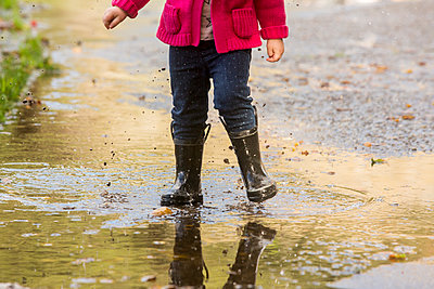 Caucasian girl wearing boots splashing in puddle - p555m1482029 by Adam Hester