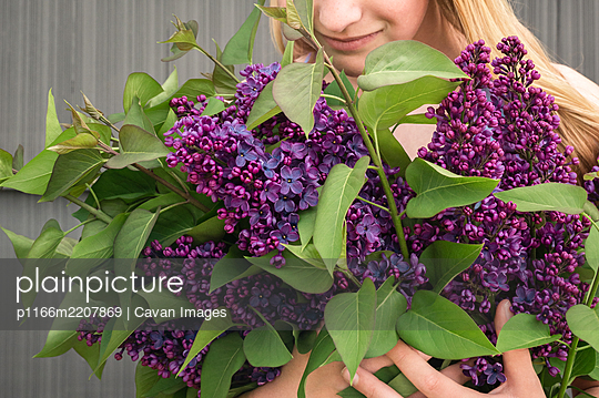 Young Girl Holding Purple Lilac Bouquet Looking Down and Smiling - p1166m2207869 by Cavan Images