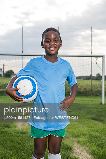 Portrait of smiling young football player holding ball on football ground - p300m1581427 von Fotoagentur WESTEND61