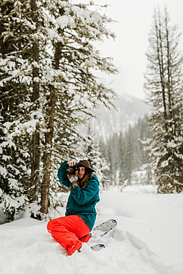 Woman photographing with camera while crouching on snow covered field in forest - p1166m1534305 by Cavan Images