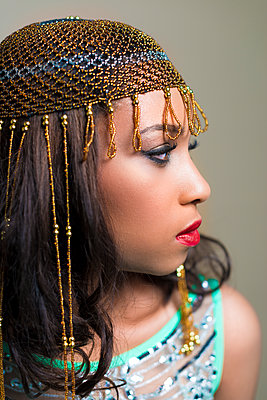 Young black woman in  exotic gold headdress. - p1433m1589021 by Wolf Kettler