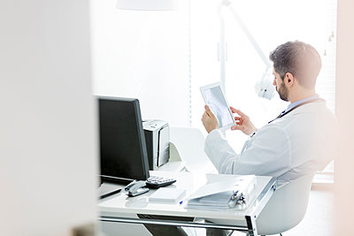 Doctor sitting at desk looking at digital tablet - p300m1166814 by Milton Brown