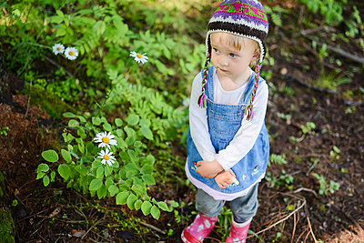 Portrait of sad little girl wearing knitted hat and denim dress outdoors - p300m2069537 by Petra Silie