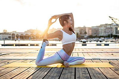 Asian woman practicing yoga on a pier at harbour at sunset, swan pose - p300m2144295 by Rafa Cortés