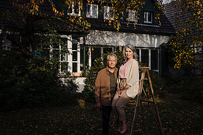 Senior couple with a ladder in garden of their home - p300m2155230 by Gustafsson