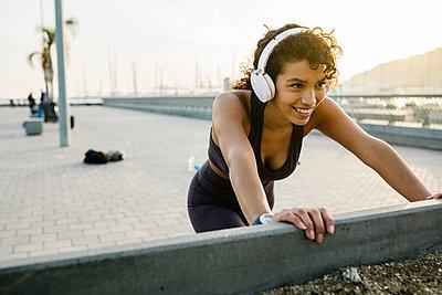 Smiling sportswoman listening music through headphones while exercising on bridge - p300m2276744 by Xavier Lorenzo