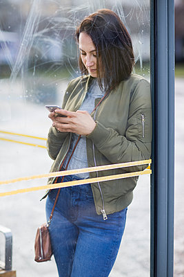 Woman on bus stop using cell phone - p312m1187736 by Susanne Walstrom