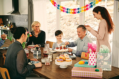 Multi-generation family enjoying birthday cake at table during party - p426m1580214 by Maskot