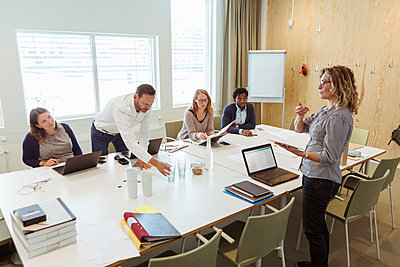 Businesswoman giving presentation to colleagues at conference table in meeting - p426m2088518 by Kentaroo Tryman