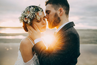 Caucasian bride and groom on sunny beach - p555m1303663 by Sophie Filippova