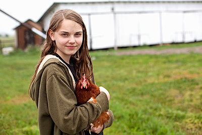 Girl carrying hen - p924m821700f by Vicky Kasala