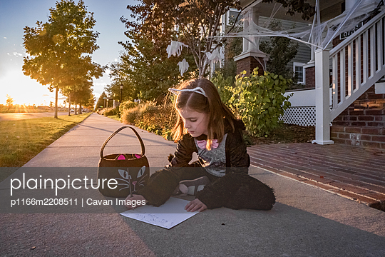 A young girl in a cat costume writes a note to the toothless fairy - p1166m2208511 by Cavan Images