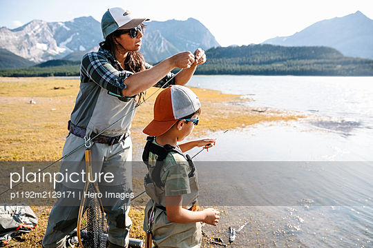 Mother and son preparing fishing poles at sunny lakeside - p1192m2129171 by Hero Images