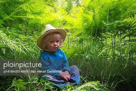 Kleiner Junge mit Strohhut sitzt im Gras - p1418m2014909 von Jan Håkan Dahlström