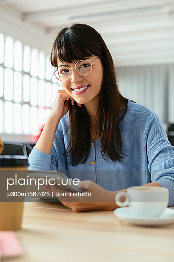 Portrait of smiling young woman with notepad at desk in office - p300m1587425 von Bonninstudio