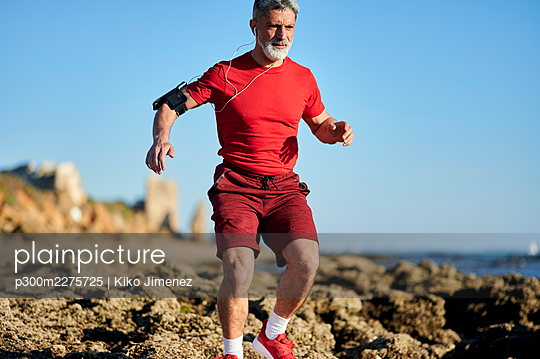 Man running through rocks on beach during sunny day - p300m2275725 by Kiko Jimenez