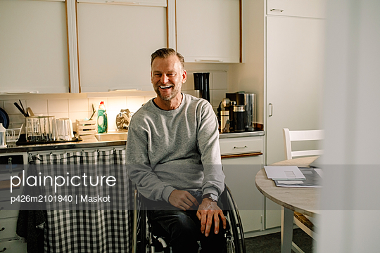Cheerful mature man sitting on wheelchair in kitchen at home - p426m2101940 by Maskot