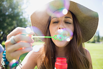 Close up woman in hat blowing bubbles in sunny summer park - p1192m1184135 by Hero Images