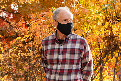 Senior man wearing protective mask in autumn park - p1427m2271710 by Steve Smith