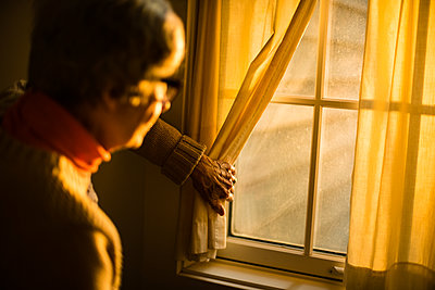 Elderly woman looking out of window - p1614m2211833 by James Godman