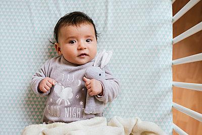 Portrait of baby girl lying in crib with toy bunny - p300m1417141 by Gemma Ferrando