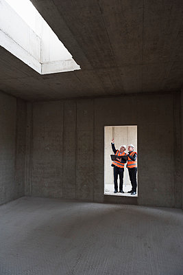 Two men wearing safety vests talking in building under construction - p300m1460446 by Daniel Ingold