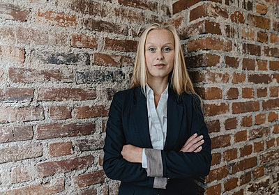 Portrait of a confident young businesswoman at a brick wall - p300m2160133 by Gustafsson