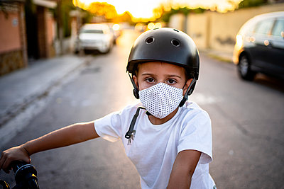 Boy wearing protective face mask and helmet on bicycle during sunset - p300m2250385 by Albert Martínez