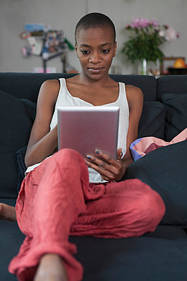 Young woman using digital tablet on sofa at home - p301m961062f by Halfdark