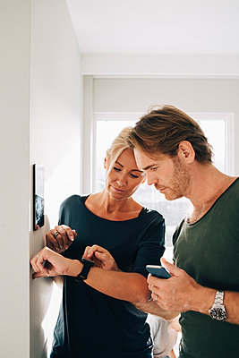 Mature couple adjusting smart watch with digital tablet mounted on wall at home - p426m1555851 by Maskot