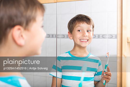 Kleiner Junge putzt sich die Zähne vor dem Spiegel - p1325m1452516 von Antje Solveig
