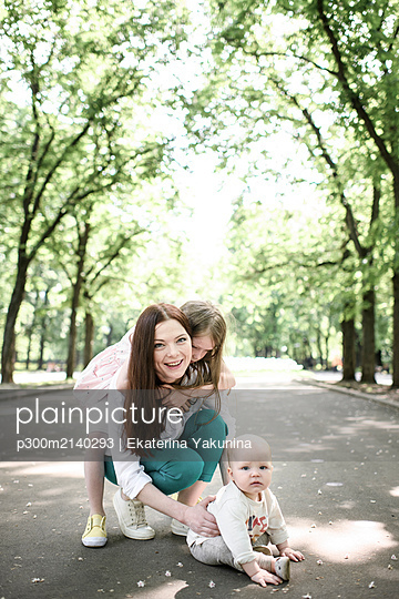 Smiling mother with her two kids in the park - p300m2140293 by Ekaterina Yakunina
